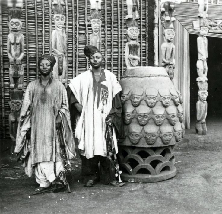 Africa   The son's of the Sultan (King Njoya) standing next to a Drum at the entrance of the Palace, Cameroon.  ca. 1911 - 1915   ©Anna Wuhrmann