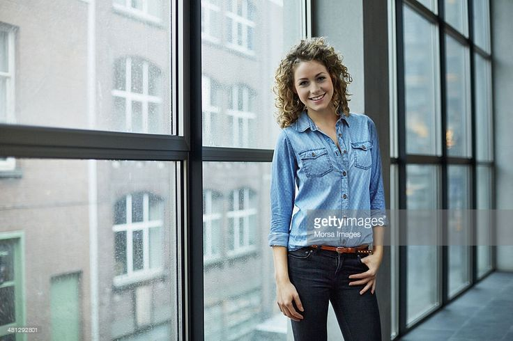 Portrait of young smiling architect by window