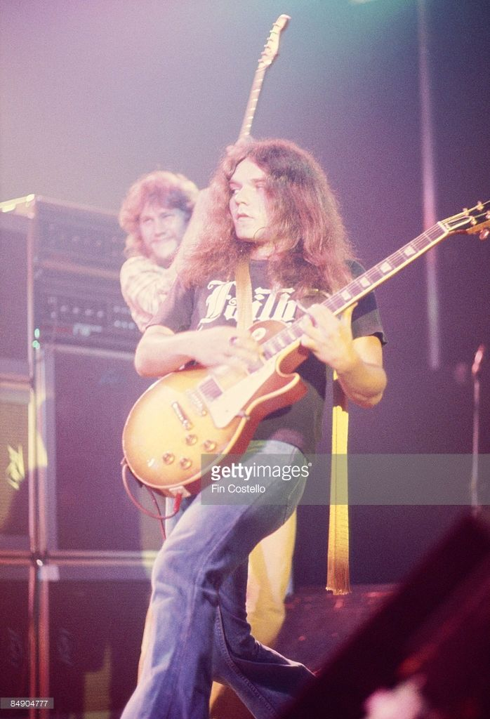 Photo of LYNYRD SKYNYRD and Gary ROSSINGTON and Steve GAINES; Gary Rossington and Steve Gaines (behind) performing on stage
