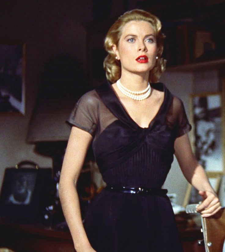 Grace Kelly photographed in black dress with belted waist in 'Rear Window'
