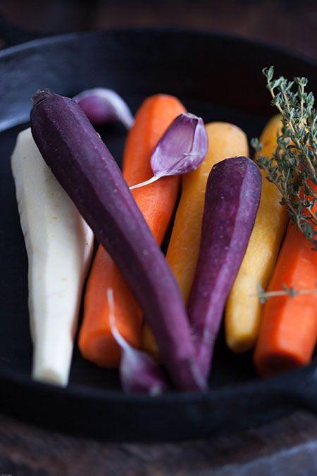 WORTELEN & PASTINAAK UIT DE OVEN MET HONING EN FETA Verwarm de oven op 180 graden. Schil de wortelen en de pastinaken. Snij de wortelen en pastinaken doormidden, halveer de helften van de pastinaak zodat ze min of meer dezelfde grootte hebben als de wortelen. Leg ze in een ovenschaal en meng met wat olijfolie en honing zodat ze goed onder zitten. Leg de knoflooktenen erin, het takje tijm en bestrooi met peper en zout. Zet 45 minuten in de oven waarbij je regelmatig de groenten omschept.