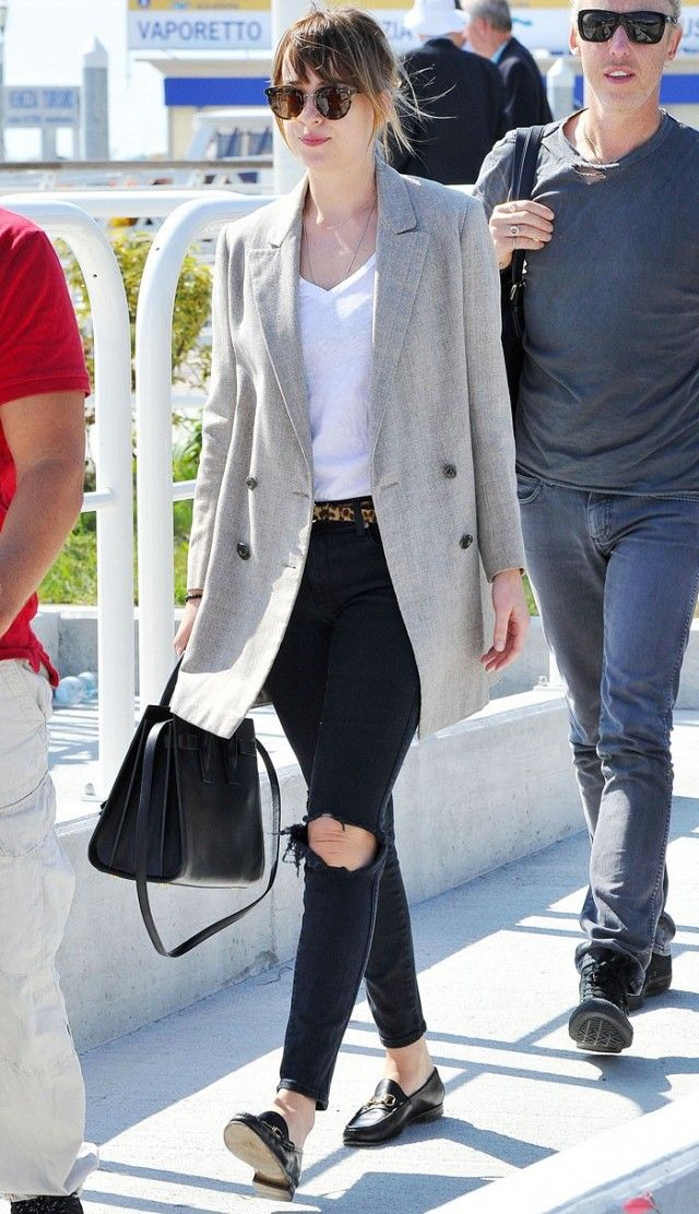Dakota Johnson wears a v-neck t-shirt, gray blazer, distressed skinny jeans, a leopard-print belt, Saint Laurent tote bag, Gucci loafers, and tortoiseshell sunglasses