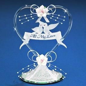 """This exquisite Blown Glass Dove Cake Top will be a delightful accent on your big day! This hand-crafted classic presents two frosted doves on a romantic glass banner that reads, """"All My Love."""" The doves in this heart wedding cake top almost seem to float on their ribbon perch, with the full piece beautifully embellished with sprays of pearls and ribbon wrapped resin roses. Cake top measures 6-1/2"""" tall. These Dove Cake Toppers have dozens of uses beyond your wedding cake! They can be used to…"""