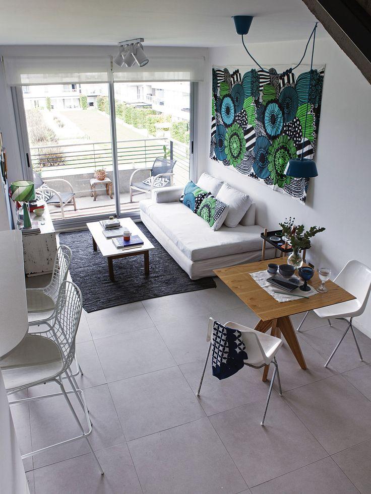Living comedor y cocina integrados en la planta baja de un duplex, con gran género de Marimekko como mural en la pared.