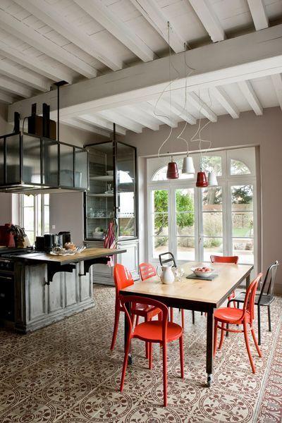 Cuisine avec des carreaux de ciment au sol qui se marient à merveille avec les chaises rouges