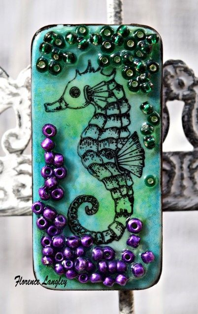 Neat idea to attach seed beads or micro beads to the surface of a rubber stamped domno. Florence Langley Sea Horse Domino broach.