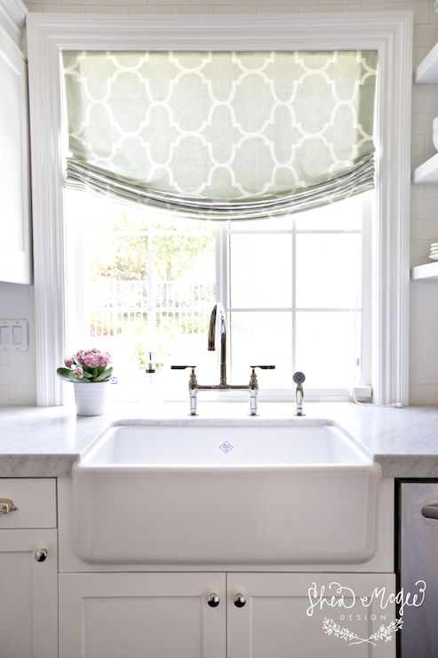 source: Shea McGee Design website    Sun filled kitchen features window covered in Windsor Smith Riad Fabric in Seafoam over farmhouse sink accented with polished nickel bridge faucet.