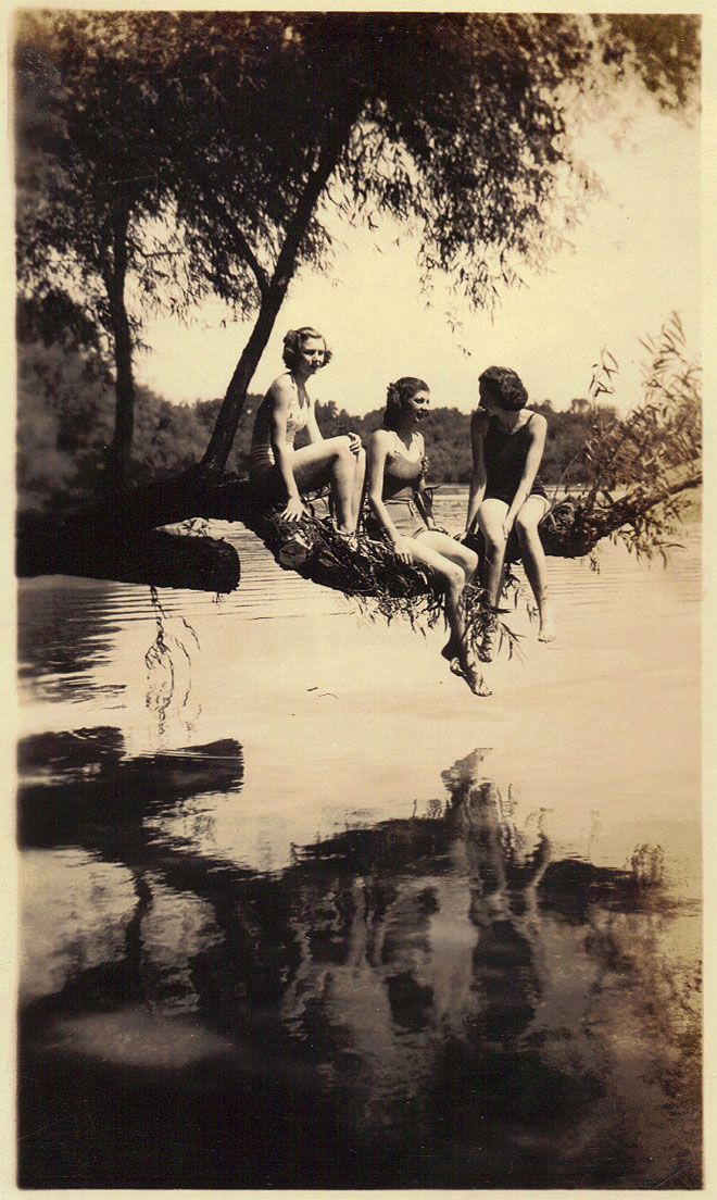 Vintage photo of 3 women (females) sitting on a tree and reflecting in the water. Sapira, togetherness, friendship, peacefull, breathtaking, history, bathing suits.