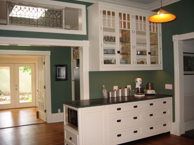 Green Kitchen Leading To A Green Dining Room   Great Victorian Kitchen.  White Cabinets With Black Pulls And Warm Wood Floor.