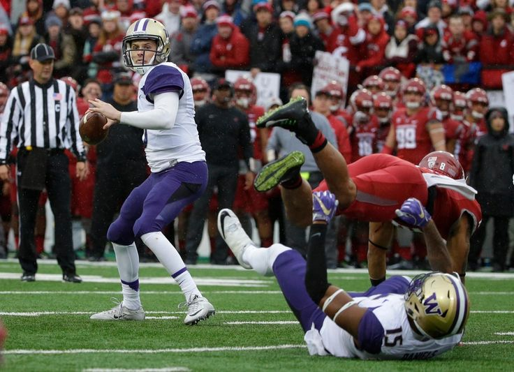 Washington quarterback Jake Browning, left, passes as Washington State safety Shalom Luani, top right, is blocked by Washington tight end Darrell Daniels, lower right, in the first half of an NCAA college football game, Friday, Nov. 25, 2016, in Pullman, Wash. (AP Photo/Ted S. Warren)