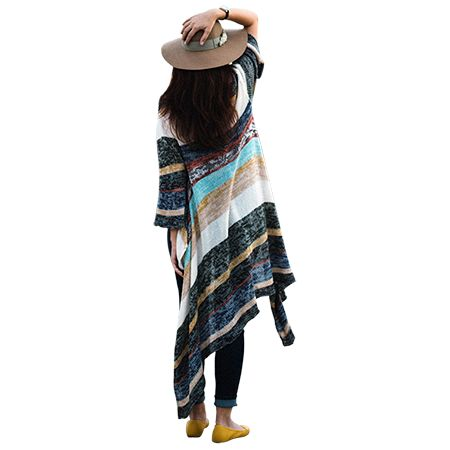 A woman wearing a blanket shirt and a wide-brimmed sun hat is standing outside.