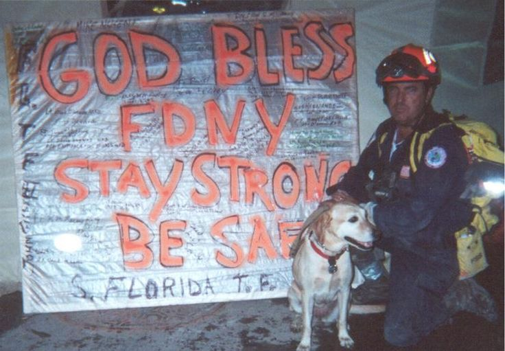 Roger Picard and Jessie of Florida Task Force 2 in front of a sign honoring New York City firefighters.