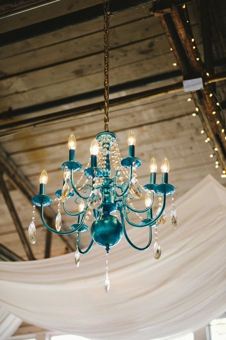 Turquoise chandelier hanging from open barn ceiling at wedding reception.