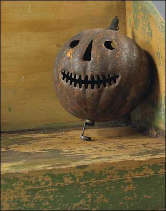 """An Early Molded and Cut Tin Halloween Candle Lantern, in the form of a jack-o-lantern with traces of the original orange painted finish, late 19th c., Ht. 9 ½"""".     Sold at Northeast Auctions August 6, 2011."""