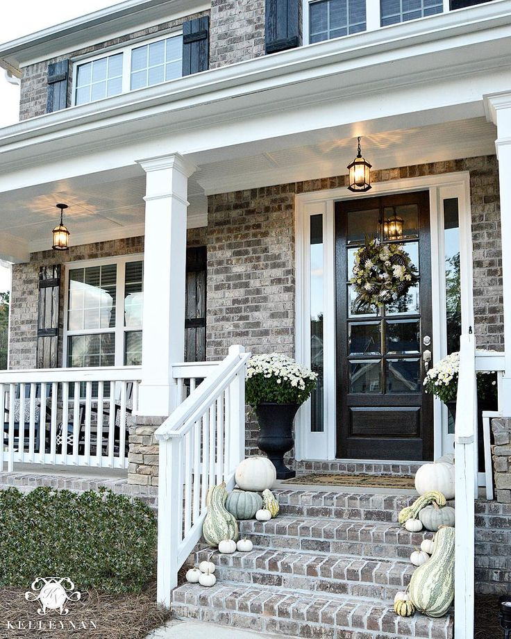 Kelley Nan (@kelleynan) • Instagram Neutral fall front porch with white and cinderella pumpkins and gourds | white mums in black urns on either side of front door | white raining on brick front porch KELLEYNAN.com