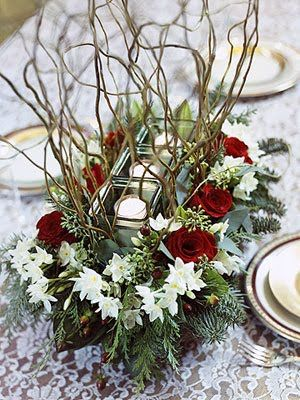This stunning arrangement was created out of a foam block to keep the flowers fresh. The arrangement was layed over top with some rectangular glass votives and twigs to add dimension and texture.