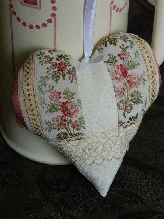 COUSSIN DE PORTE FAIT MAIN COEUR TISSU PRECIEUX ANCIEN DENTELLE DE BROCANTE Un très beau tissu soyeux aux roses anciennes est mis en valeur sur le devant du cœur. Il est souligné par une large dentelle ancienne neuve en deux tons d'écru. Pour une douceur extrême le reste du cœur (devant et arrière) est confectionné dans une belle toile écrue très pâle. Il est entièrement doublé ce qui lui procure une tenue optimale. Ce coussin mesure 17 cm de haut x 16 cm de large.
