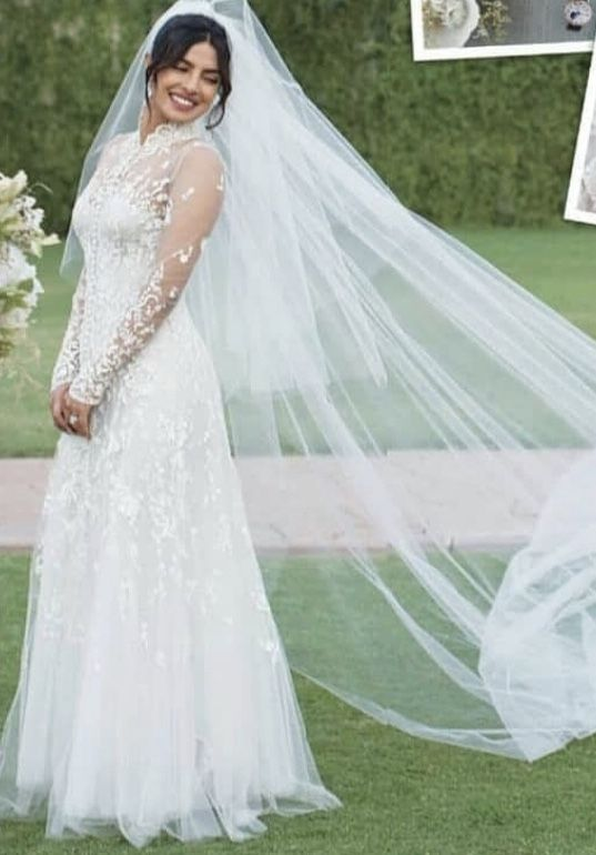 dfa73b4f1c Priyanka Chopra s wedding dress and veil. We love the vintage inspiration  of her gown. The high collar and the lace long sleeve looks absolutely  stunning on ...
