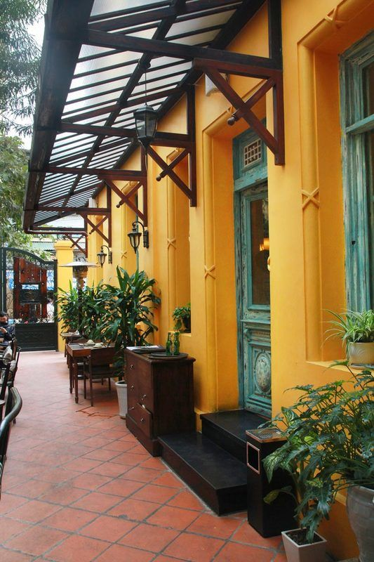 """The dark wooden sign is hung outside, saying: """"HOME – Vietnamese Restaurant"""".Despite the busy lunch time coming, the gate was still closed as always and only open once I decided to come in. Situated in a villa built in French colonial style, Home could be found easily. Its bright yellowwalls and faded green windows made up an outstanding appearance, setting the restaurant apart from the humble neighborhood which surrounds Chau Long market #review #eatinginhanoi #restauraunt"""