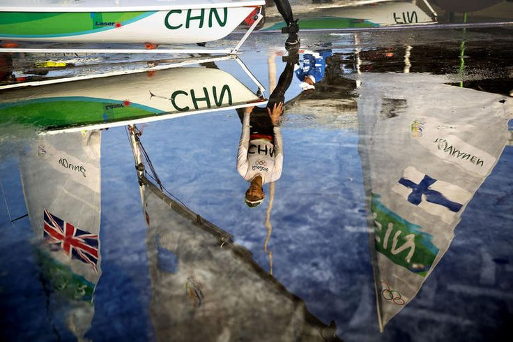 China's Xu Lijia is reflected in a puddle as she hoses off her boat after competing in the Laser Radial women sailing race at the 2016 Summer Olympics in Rio de Janeiro, Brazil, Aug. 9, 2016.Photo by David Goldman/AP