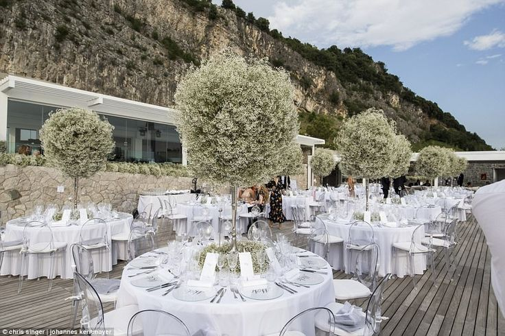 Baby's Breath wedding reception centerpieces.  The wedding breakfast took place on the decking at the area's only five-star hotel and tables were decorated with simple trees and place mats with the couple's initials emblazoned on