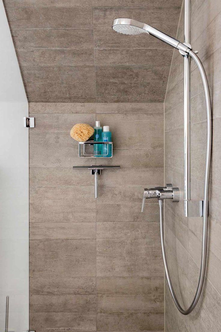 Dusche mit Handbrause, Brausestange, links Glaswand, geradezu Wand mit Dachschräge, darunter Abzieher und Duschkorb