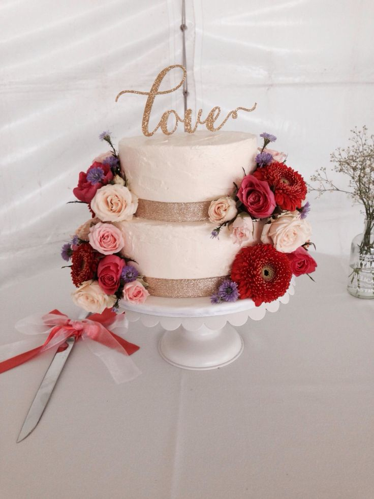 A gorgeous buttercream wedding cake with fresh blooms created by Michelle-Marie's Kitchen. Topper by A La Roche
