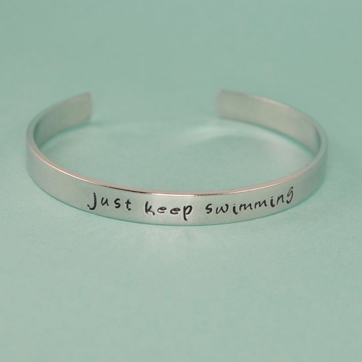 """The bracelet is hand stamped with """"just keep swimming"""" from Finding Nemo. The bracelet measures 1/4"""" x 6"""" and is adjustable to fit all sizes. The Details •Handcrafted using 1/4"""" width aluminum, brass,"""