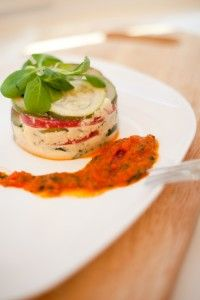 Timbales of tomatoes and zucchini with a spicy tomato sauce.