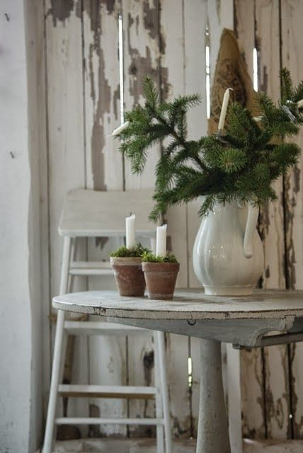 Simple~ ironstone pitcher full of green branches and white candles in pots.