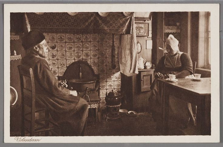Man en vrouw in dracht in Volendams interieur bij de haard, een betegelde schouw. 1910-1914 #NoordHolland #Volendam