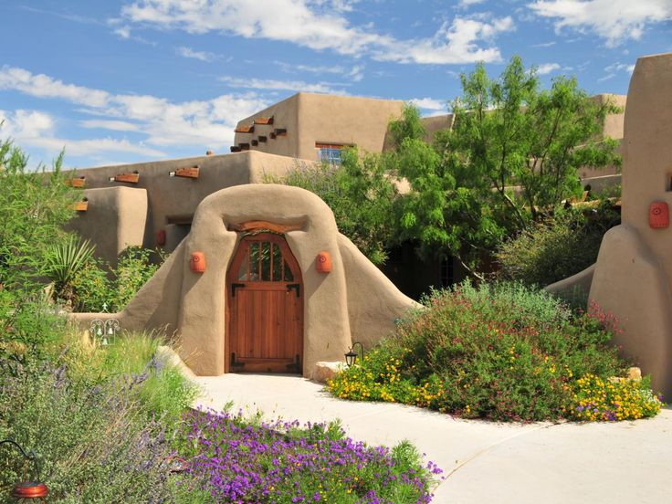 the exterior of this new mexico adobe style home uses orange paint and native plants - Southwestern Adobe Style House Plans