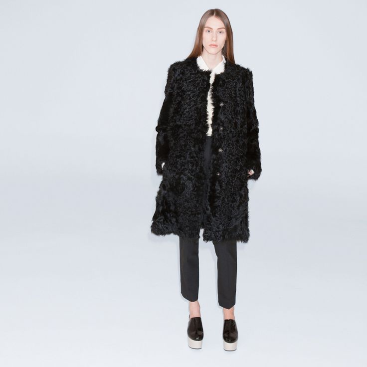 The Trip is a long lamb shearling coat with press buttons at front, slit in center back and in seam pockets.