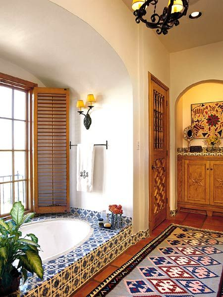 Beautiful blue-and-white Mexican tiles and arched details give this room a distinctly Southwestern flair. A built-in tiled soaking tub, placed in an alcove, looks out over the back yard. To keep the tile the focal point of the room, the other aspects of the design are quite simple. The long, colorful rug is a nice counterpoint to the Mexican tile. (Photo: Photo: Laurey W. Glenn; Stylist: Lisa Powell)
