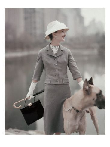 Vogue - February 1956 Model holding great dane, wearing gray suit and hat, with white gloves; she holds handbag and umbrella with caned handle.