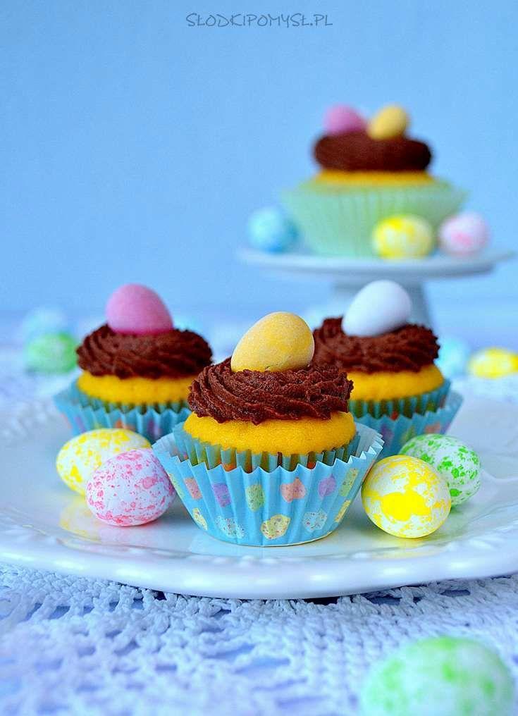 Babeczki cytrynowe zkremem czekoladowym naWielkanoc. Przepyszne babeczki cytrynowe zostały nasączone sokiem cytrynowym i udekorowane czekoladowym kremem i kolorowymi mini jajeczkami.