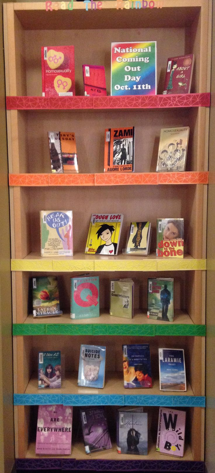 Read the Rainbow library display in honor of national coming out day, rainbow book covers , all books feature LGBT fictional charaters or are non-fiction LGBT themed books library display ideas