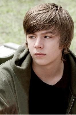 Miles Heizer as Alan Bartram, a quiet, sullen teen boy who dreams of a life beyond Hollow Valley when his religious convictions begin to falter.