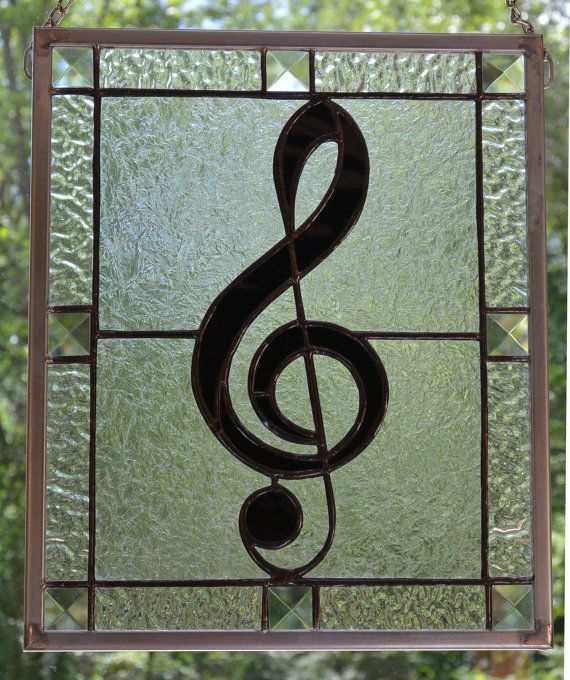 Treble Clef stained glass hanging for a real music lover. It is constructed using black glass for the treble clef and clear textures for the background. This piece sparkles when in sunlight. The border features clear 1x1 bevel squares. The size is 11 1/2 X 12 1/2 which makes it an easy gift to ship to someone you know. The piece comes complete with a hanging chain. It can also be custom made to order in as little as a week using colors of your choosing.