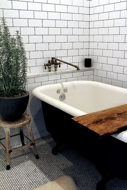 White subway tile with dark grout. Love the black claw foot tub and that rustic bath shelf is fabulous!