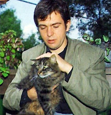 Peter Gabriel strokes a cat like it's about to detonate in his face.