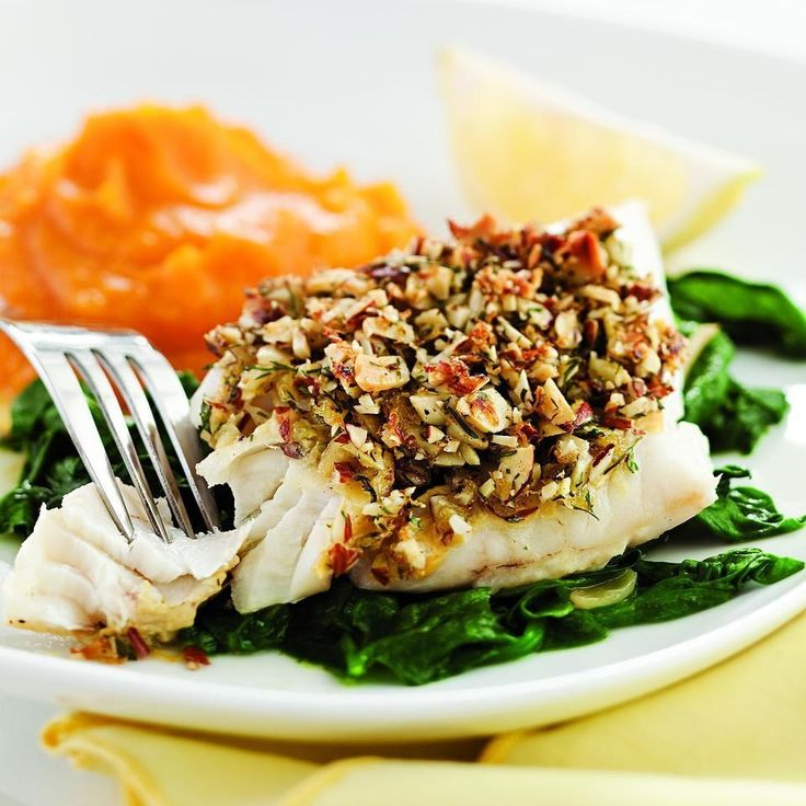 Coating fish with nuts and baking it is an easy, foolproof way to cook it elegantly. And it is especially nice with a mild white fish like cod or halibut. The spinach turns a little yellowy because it's cooked with the acidic lemon juice, but what you lose in green color is more than made up for in great flavor.