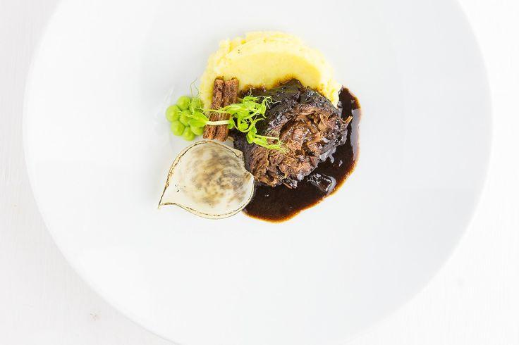 Geschmorte Ochsenbäckchen mit einem würzigen Kartoffel-Aioli-Püree, Erbsen, eingelegter Zwiebel und Leberwurst-Tramezzini.