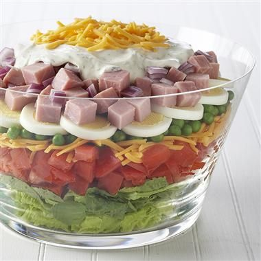 Layered Salad 4c salad greens 2 tomatoes chopped 2c shredded cheese 1c thawed peas 3 hard cooked eggs 2c ham cubed 1/2c chopped red onion 1/2c mayonnaise 1/2c sour cream 1tsp dill weed 1/2tsp mstard, ground layer greens, tomato, cheese, peas, eggs, ham onion. mix mayo, cream, and spices spread evenly over salad. refrigerate 1hr or overnite, sprinkle with cheese. enjoy