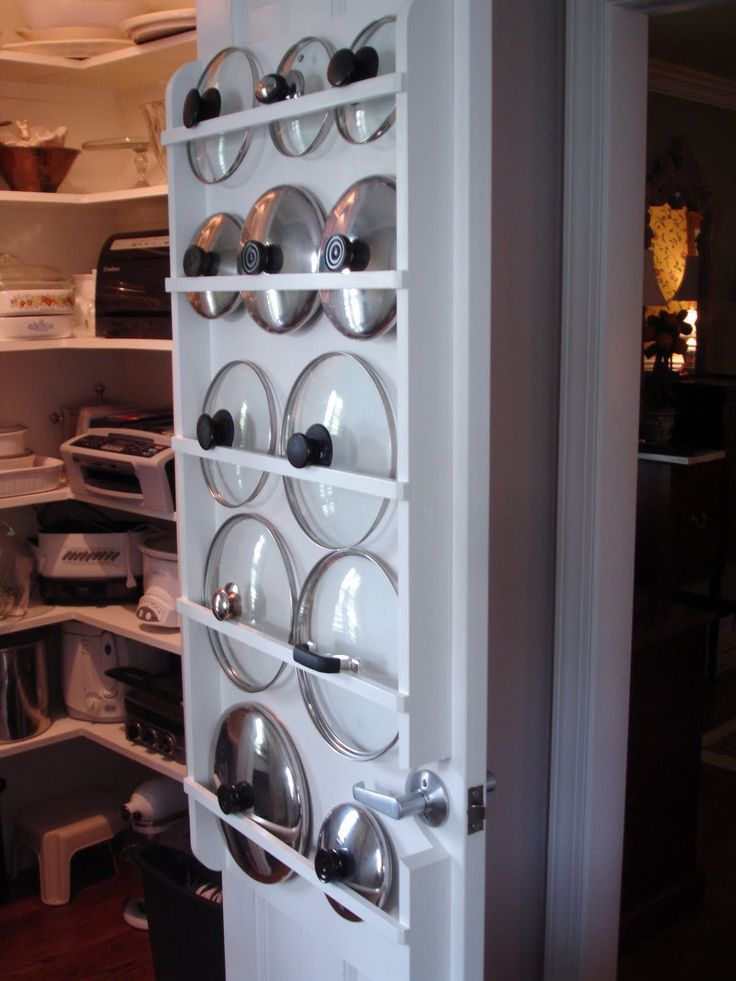 Pot lids organized on the back of a pantry door
