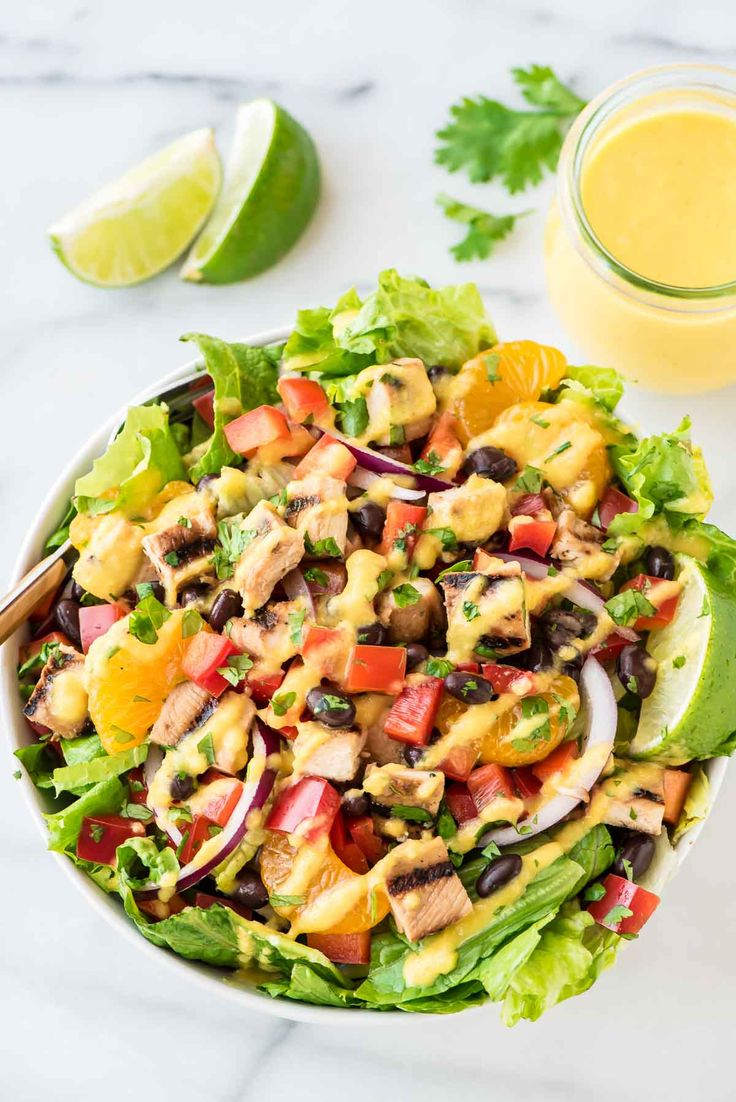 Grilled Caribbean Chicken Salad with 5 Minute Mango Dressing. WAY better than your favorite restaurant salad at a fraction of the cost! Packed with juicy chicken, crunchy veggies, black beans, and the best tangy mango dressing! @wellplated