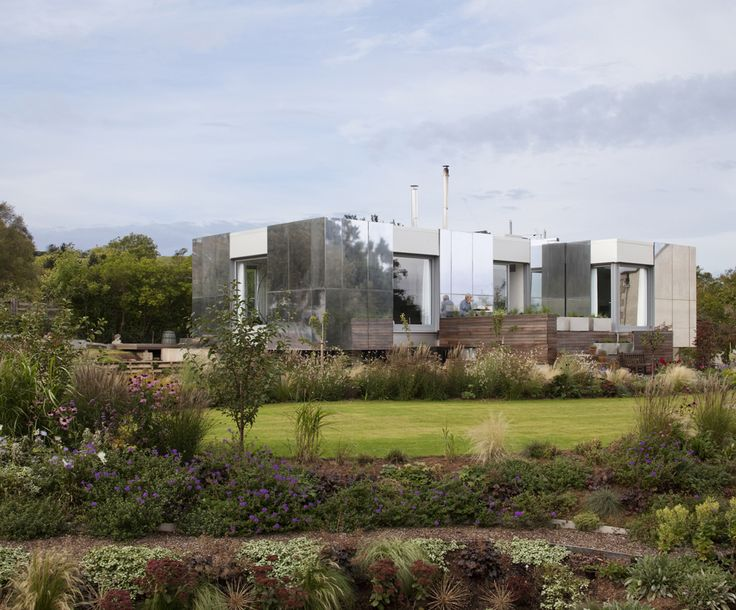 The exterior is clad in an intelligent skin of bespoke full-height panels, which are electronically motorised to slide open fully. The panels are highly insulated and allow the occupants to control and vary the thermal performance of the house depending on the time of the day and year. An aluminium coating reflects the surrounding gardens ensuring that the house recedes into its setting.Green Orchard / Paul Archer Design
