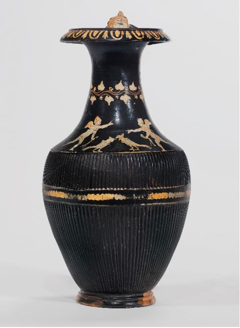 Gnathian oinochoe, attributed to the Volcani Painter, late 4th century B.C. With foot in two degrees, ribbed body, overhanging rim, and ribbed handle with each attachment plate molded in the form of a maenad head with long flowing hair, the shoulder decorated with two erotes attending a cock-fight, a wreath of ivy around the neck, the details in added yellow and White, 33 cm high. Private collection