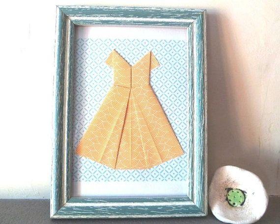 Collage origami, robe jaune sur papier origami bleu clair et blanc. Vendue sous cadre bois bleu clair, cérusé blanc, qui peut être accroché au mur ou posé sur une table. Convient parfaitement à la décoration dune chambre de fillette ou dune jeune fille Dimensions : 24 cm de haut sur