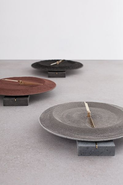Monti Silvestri Clock by Studio Formafantasma tells time with brass fittings circling a crater of powdered volcanic rock, set on a base of lava-formed basalt, witness to the impact of eruption on the place where it occurred.